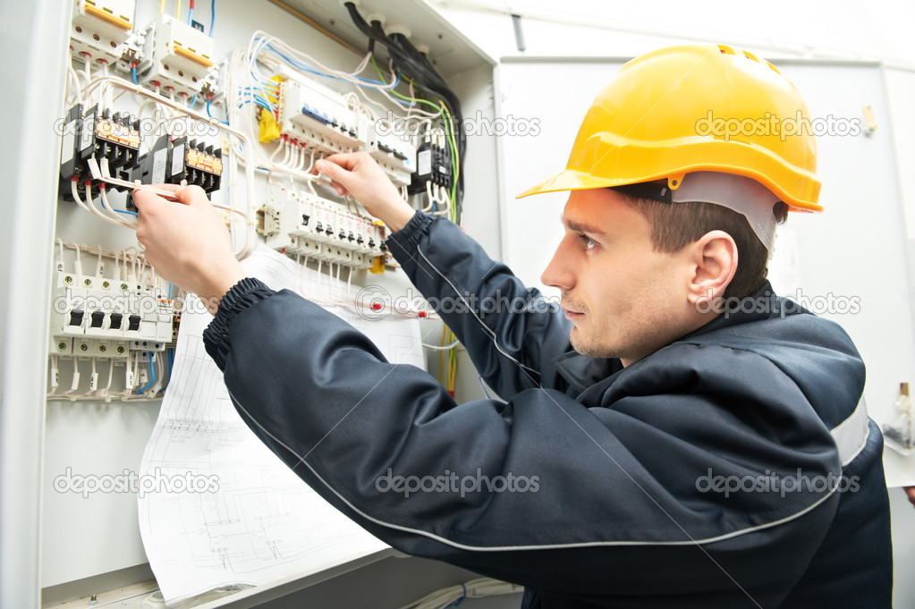 One electrician builder at work with assembly drawing inspecting high voltage power electric line distribution fuseboard — Stock Photo #9700307