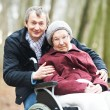 Old senior woman in wheelchair with careful son — Stock Photo #9734694