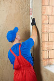 Construction worker plasterer with level — Stock Photo