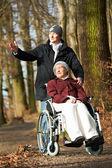 Femme âgée en fauteuil roulant, marche avec fils — Photo