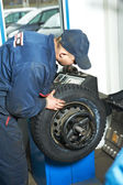 Machanic repairman at tyre balancing adjustment — Stock Photo