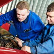 Stock Photo: Two car mechanic diagnosing auto engine problem