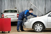 Car mechanic diagnosing auto engine problem — Stockfoto