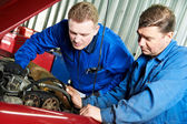 Two car mechanic diagnosing auto engine problem — Stock Photo