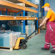 Worker with fork pallet truck — Stock Photo #9873879
