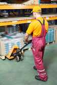 Worker with fork pallet truck — Stock Photo