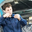 Stock Photo: Car mechanic inspecting engine sparking plug