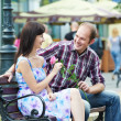 Man and girl with flower at street bench on a date — Stock Photo