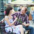 Man and girl with flower at street bench on a date — Stock Photo #9927443