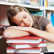 Tired young woman sleeping on book in library — Stock Photo