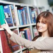 Young adult student selecting book in library — Stock Photo