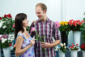 Man and girl with flower at shop on a date — Stock fotografie