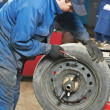 Machanic repairmat tyre balancing adjustment — Stock Photo #9938395