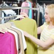 Young woman at clothes shopping store - Stock Photo