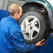 Mechanic installing car wheel at service station — Stockfoto