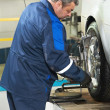 Auto mechanic at wheel alignment work — Stock Photo