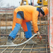 Stock Photo: Builder worker pouring concrete into form