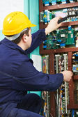 Electrician checking current at power line box — Stock Photo
