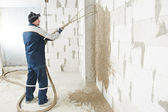 Plasterer at stucco work with liquid plaster — Stock Photo
