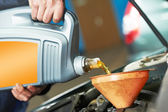 Closeup mechanic hand pouring oil into car motor — Stock Photo