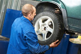 Mechanic installing car wheel at service station — Stock Photo