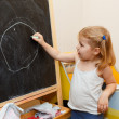 Stock Photo: Girl drawings with chalk on blackboard