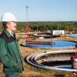 Stock Photo: Mature mmanual worker in white hardhat near sewage treatment basin