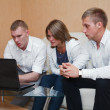 Three young sitting on sofa and looking at laptop screen. — Stock Photo