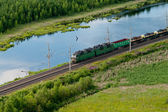 Railway transportation. Freight train between evergreen woods. Aerial view — Stock Photo