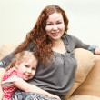Mother and her little daughter sitting and couch and hugging — Stockfoto #8743308