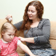 Mother and little daughter sitting on couch. Woman combing daughter hair — Stock Photo #8743311