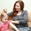 Mother and little daughter sitting on couch. Woman combing daughter hair — Stock Photo