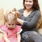 mama i córeczka siedzi na kanapie. Czesanie włosów córka kobieta — Zdjęcie stockowe #8743314