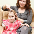 Mother and little daughter sitting on couch. Woman combing daughter hair — Stockfoto #8743317