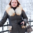 One caucasian female in winter clothes standing near rails. — Stock Photo