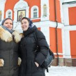 Two Russian women in winter clothes against Orthodox monastery building — Foto de Stock