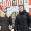 Two Russian women in winter clothes against Orthodox monastery building — Stock Photo