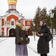 Russian women in winter clothes against Orthodox monastery — Stock Photo