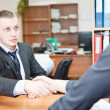 Young business man shaking hands with colleague across the table — Stock Photo