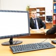 Office computer on desk and two businesspersons on background defocused — Stock Photo #8743413