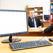 Stock Photo: Office computer on desk and two businesspersons on background defocused