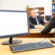 Office computer on desk and two businesspersons on background handshaking — Stock Photo