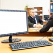 Stock Photo: Office computer on desk and two businesspersons on background handshaking