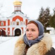 Russian female pilgrim in winter clothes against monastery — Foto Stock