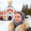 Russian female pilgrim in winter clothes against monastery — 图库照片