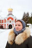 Peregrino feminino russo em roupas de inverno contra mosteiro — Fotografia Stock