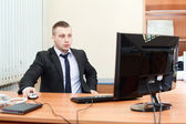 Portrait of a smart young businessman working on computer at office — Stock Photo