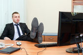 Handsome young business man resting with feet on desk — Stock Photo