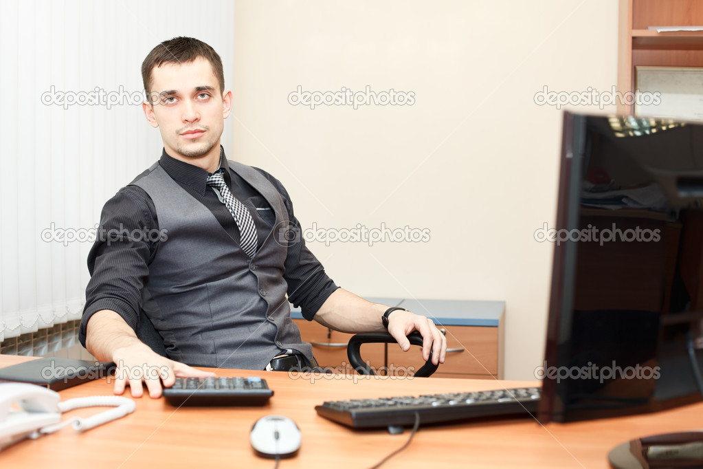Young business man sitting at table and working on computer — Stock Photo #8743434