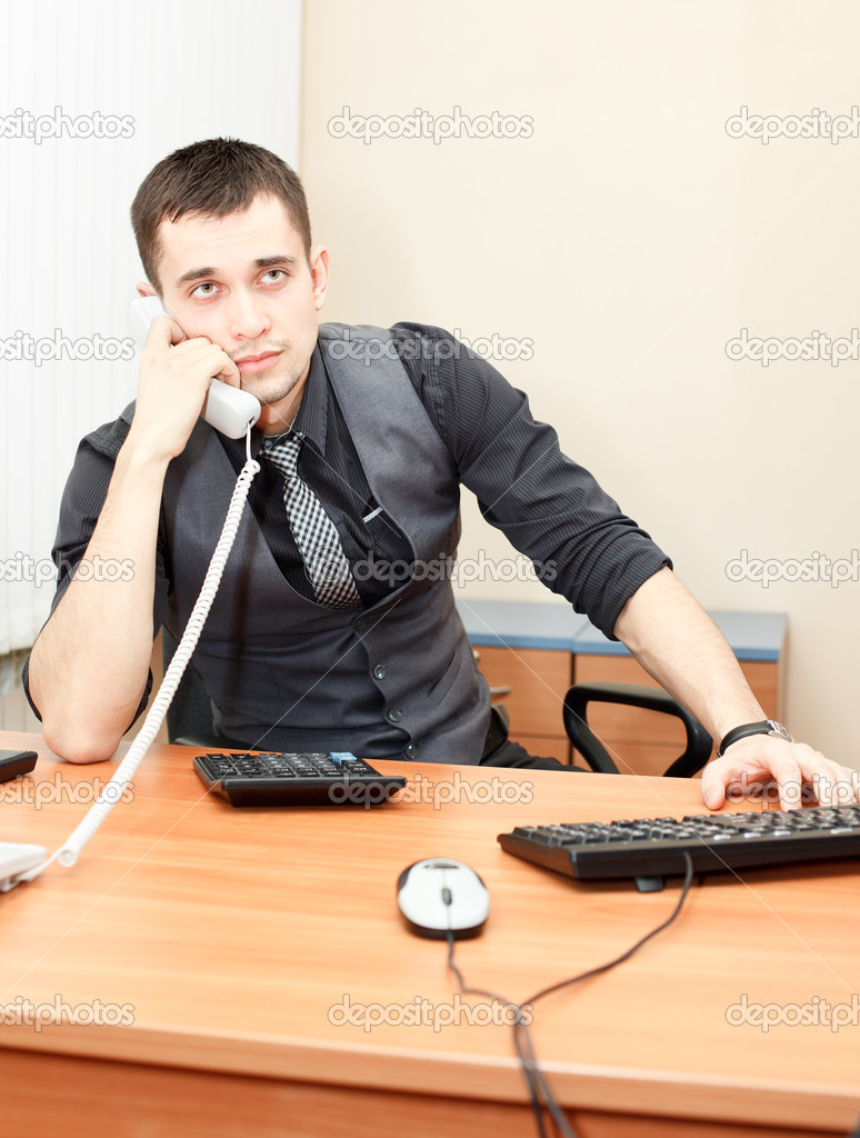 Smart businessman speaking on phone while working on desktop computer — Stock Photo #8743444